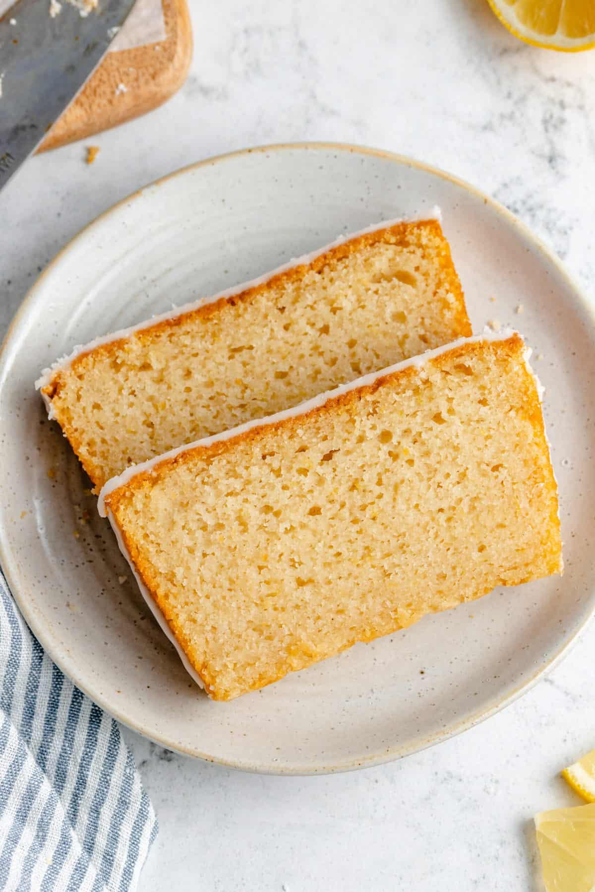 Two slices of glazed lemon loaf cake.