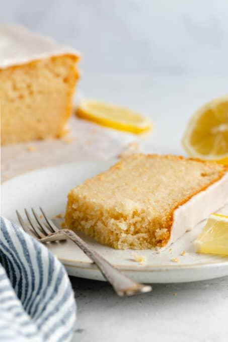A slice of vegan lemon loaf cake with a fork.