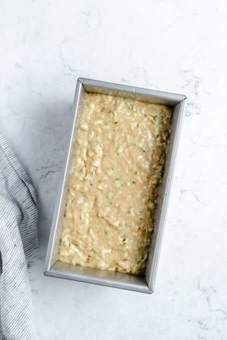 Zucchini bread batter in a loaf pan.