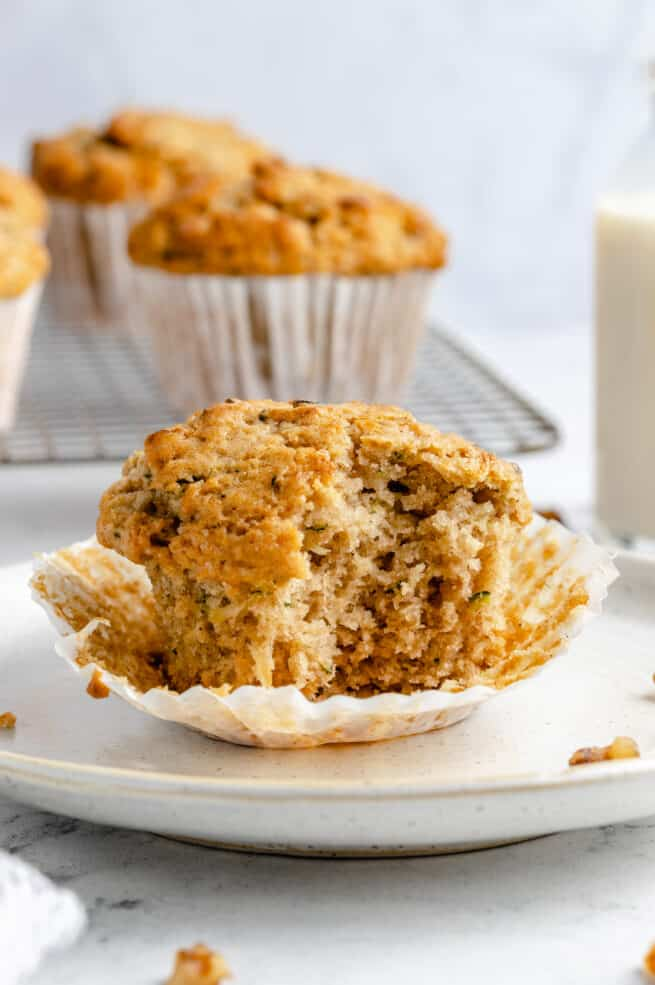 Zucchini muffin with a bite taken out of it.