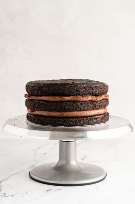 three layers of chocolate cake stacked with frosting in the inside