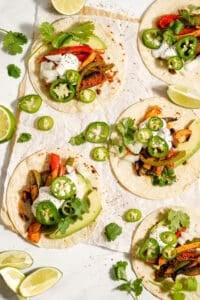 Vegan fajitas with jalapeno slices and lime wedges.
