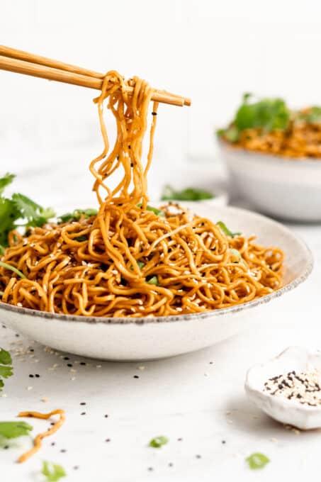 Chopsticks holding sesame noodles.