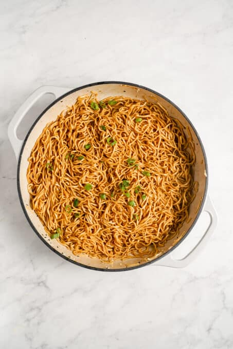 Sesame noodles in a pot with chopped green onions.