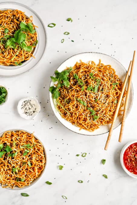 A plate of noodles with garnish and chopsticks.