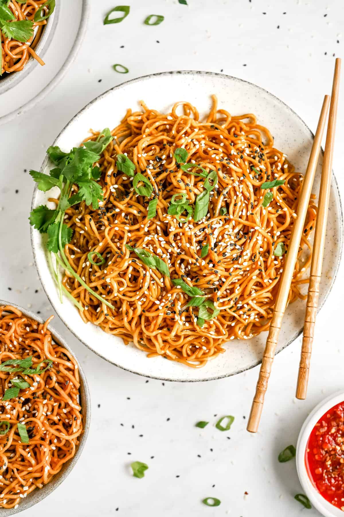 A plate of vegan sesame noodles with garnish.