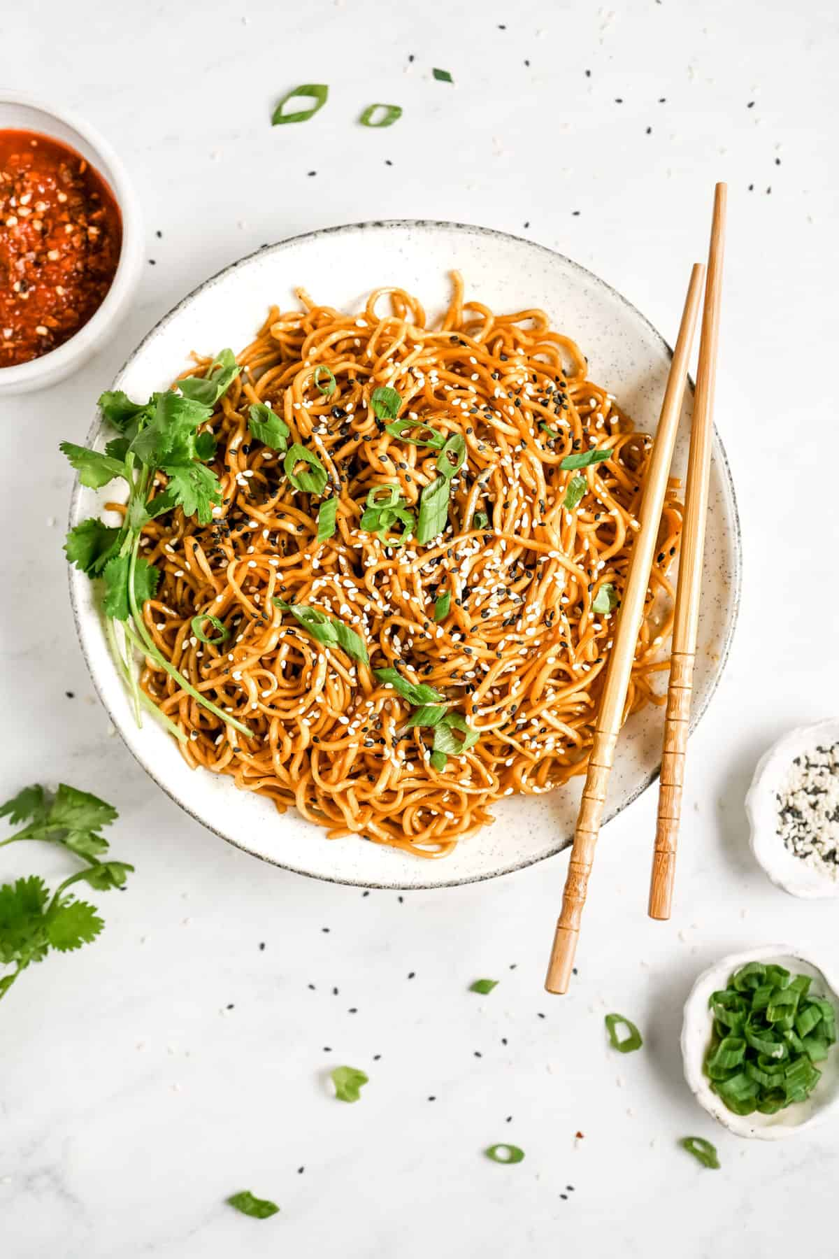 A plate of Chinese noodles with chopsticks.