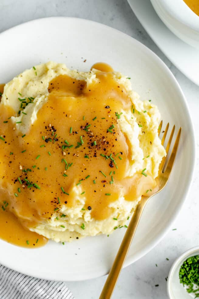 Overhead shot of mashed potatoes on white plate topped with gravy