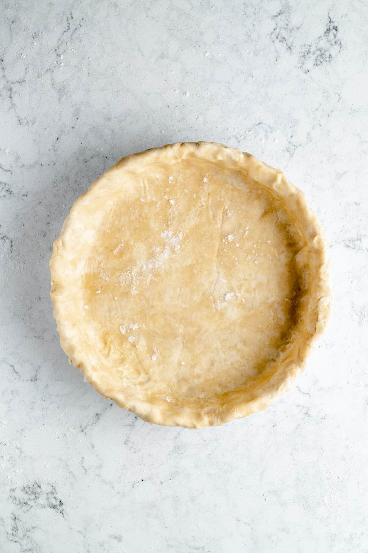 Vegan pie crust in a baking dish.