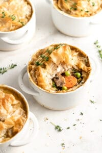 Vegan pot pies in white ramekins, center pie with filling visible