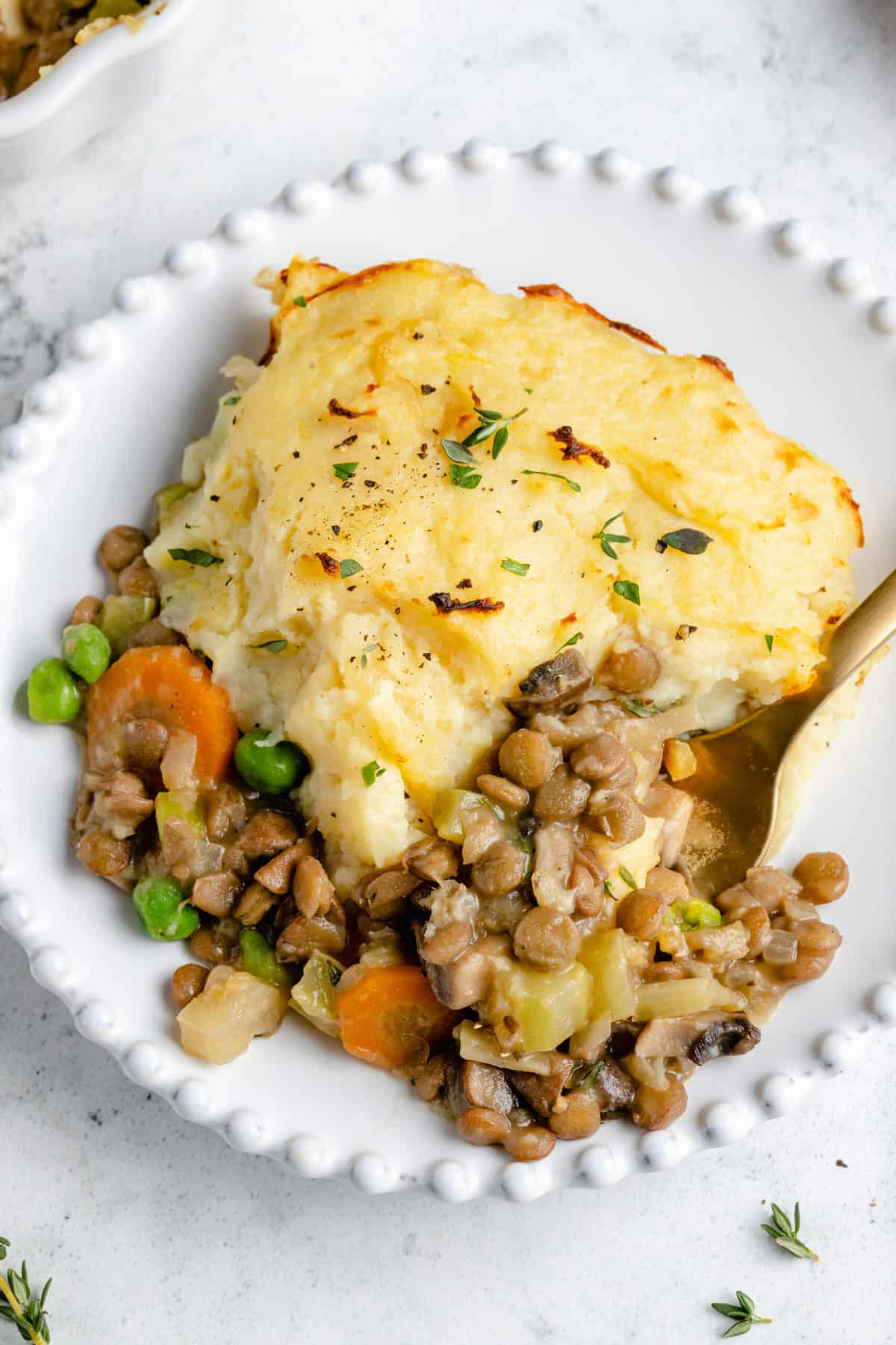Serving of Vegan Shepherd's Pie on white plate with fork