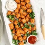 Overhead view of sweet potato tots on white platter with dipping sauces in bowls
